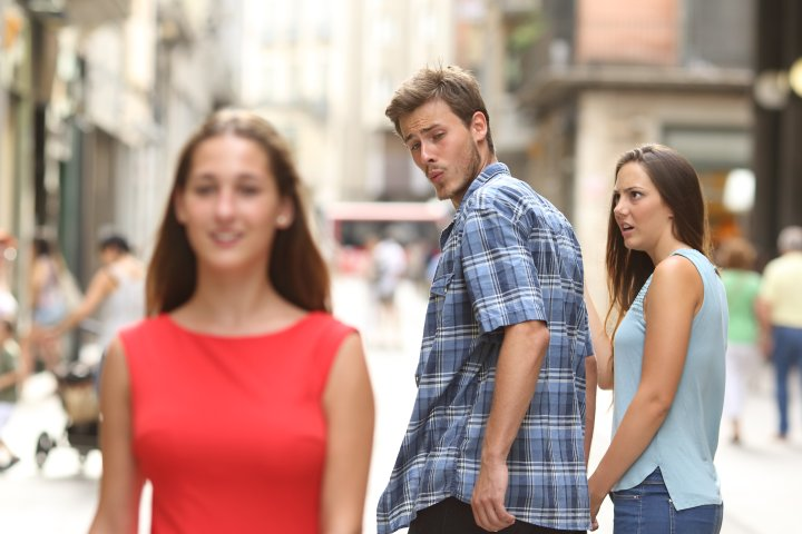Disloyal man with his girlfriend looking at another girl